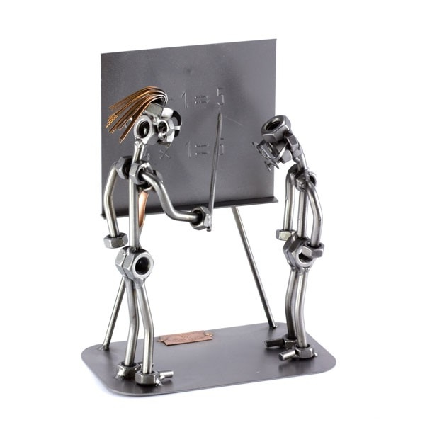 A photo of a Female Steelman Teacher with a student in front of a blackboard metal art figurine