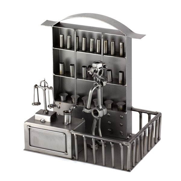 A photo of a Steelman Pharmacist in between his large apothecary cabinet and a sales counter metal art figurine